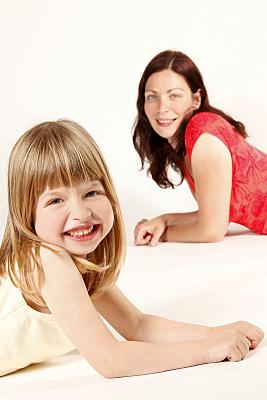 Familienfoto lächelndes, auf dem Bauch liegendes Mädchen im Vordergrund, lächelnde, auf dem Bauch liegende Mutter in rotem Top im Hintergrund.