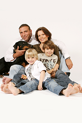 Familienfoto Vater, Mutter und zwei Kinder sitzend mit Dobermann vor hellem Hintergrund.