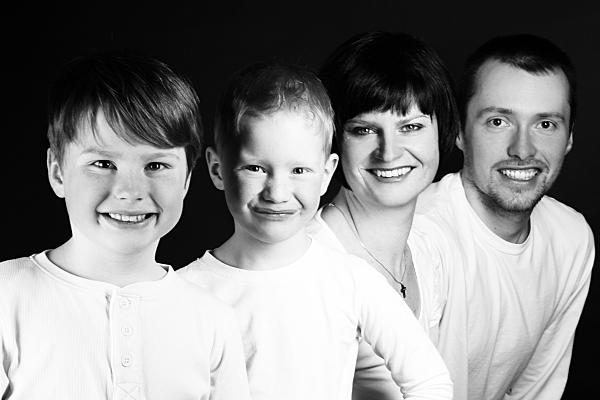 Schwarz-weiß Familienfoto Vater, Mutter und zwei Kinder in weißen Oberteilen vor dunklem Hintergrund.