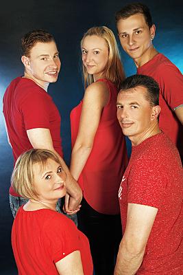 Familienfoto Eltern mit Tochter, Sohn und Freund, alle in roten Shirts und in Rückansicht vor blauem Hintergrund.