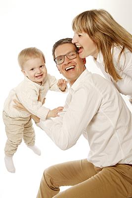 Familienfoto Vater, Mutter und Kind in weißen Blusen, der Mann hebt das Kleinkind hoch, während die Frau lachend zuschaut.