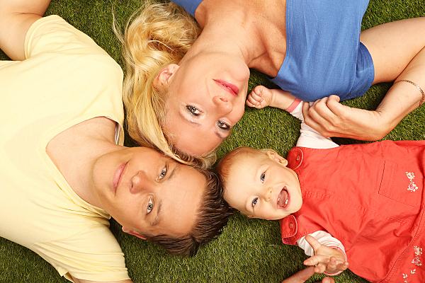 Familienfoto Vater, Mutter und Kind auf einem grünen Untergrund auf dem Rücken liegend und nach oben schauend.