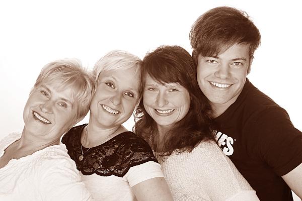 Low Key Familienfoto drei Frauen und ein Mann vor weißem Hintergrund.