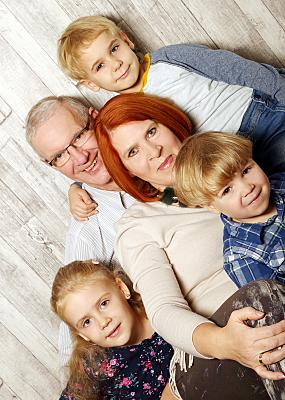 Familienfoto Vater, Mutter und drei Kinder vor einem hellen Hintergrund.