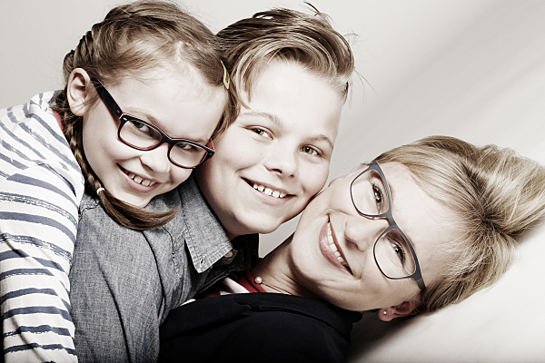 Familienfoto auf dem Rücken liegende Mutter, auf deren Bauch zwei Kinder übereinander liegen.