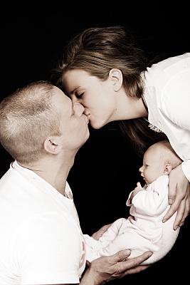 Low Key Familienfoto sich küssender Eltern, die zwischen sich das Baby halten.