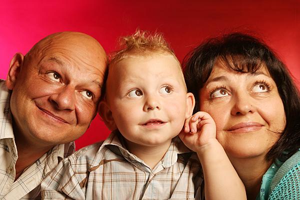 Familienfoto Vater, Mutter und Kind vor rotem Hintergrund.