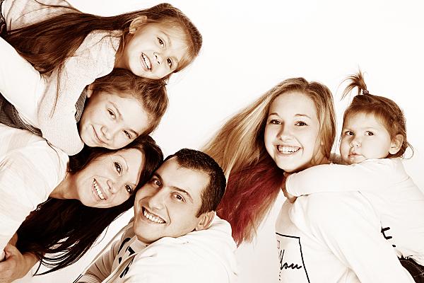 Familienfoto Eltern mit vier Mädchen, die sich alle auf die Rücken der Eltern lehnen.