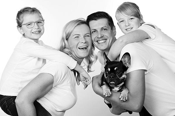Low Key Familienfoto vierköpfige Familie mit Hund, die Eltern tragen jeweils ein Kind auf dem Rücken und lehnen ihre Köpfe aneinander.