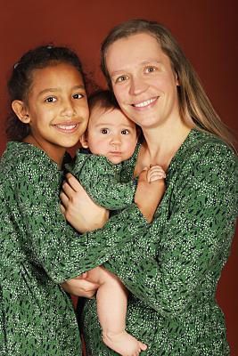 Familienfoto Frau mit zwei Kindern in grünen Blusen vor rotem Hintergrund.
