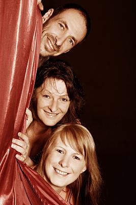 Familienfoto Mann mit zwei Frauen, die hinter einem roten Vorhang hervorschauen.