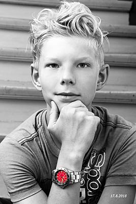Low Key Kinderfoto Junge mit kurzen blonden Haaren, der seine Hand ans Kinn hält.