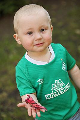 Kinderfoto erstaunt schauender Junge in grünem Shirt auf einer Wiese.