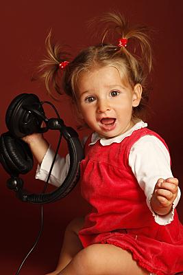 Kinderfoto erstaunt guckendes Mädchen mit rotem Kleid und zwei Zöpfen, das einen schwarzen, alten Telefonhörer in der Hand hält.
