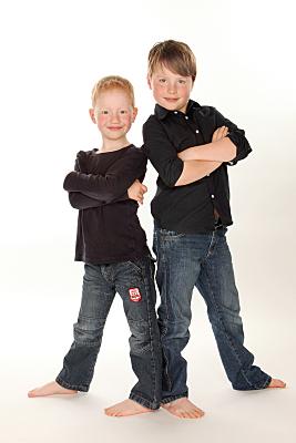 Kinderfoto zweier Jungen in dunklem Hemd und Jeans, die mit vor der Brust verschränkten Armen nebeneinander stehen und sich leicht aneinander anlehnen.