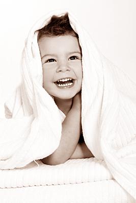 Low Key Kinderfoto in weißes Handtuch eingehülltes, lachendes Kleinkind.
