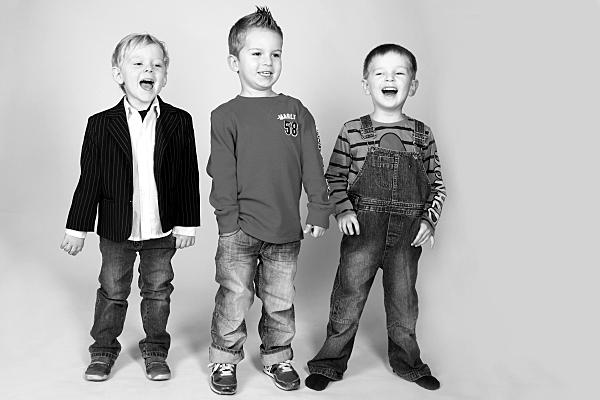 Low Key Kinderfoto von drei stehenden Jungen, die alle fröhlich lachen.