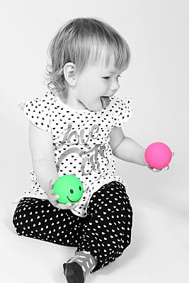 Low Key Kinderfoto sitzendes Kleinkind in gepunkteten Sachen und mit knall-grünem und pinken Ball in den Händen.