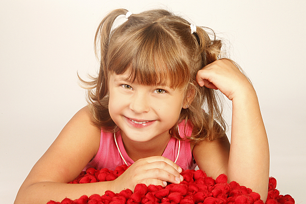 Kinderfoto lächelndes Mädchen mit zwei Zöpfen, das vor einem Haufen Rosenblätter auf dem Bauch liegt.