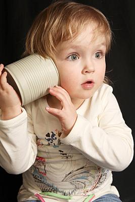 Kinderfoto staunendes Kleinkind in hellem Pulli, das sich eine helle Blechdose ans Ohr hält.