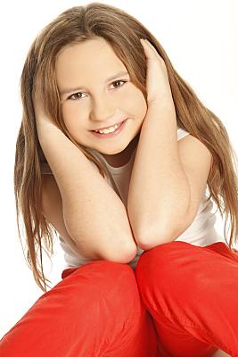 Kinderfoto lächelndes Mädchen mit langen Haaren und roter Hose, die ihre Ohren zuhält.