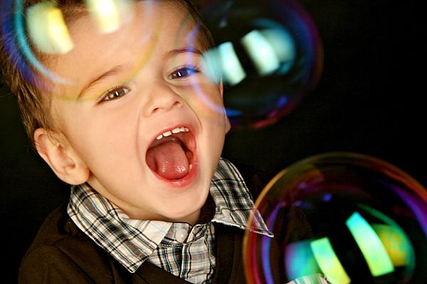 Kinderfoto lachendes Kleinkind in kariertem Hemd, das staunend Seifenblasen anschaut vor dunklem Hintergrund.