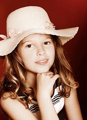 Kinderfoto lächelndes Mädchen mit Sonnenhut und geringeltem Top vor rotem Hintergrund.
