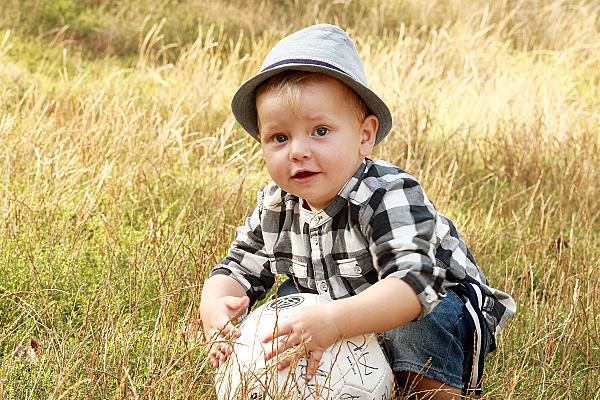Kinderfoto hockender Junge mit Hut auf einer Wiese, der einen weißen Ball festhält..