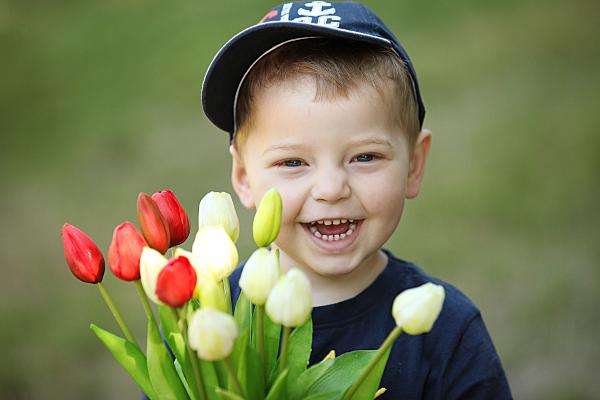 Kinderfoto lächelnder Junge mit Cap, der einen Strauß Tulpen vor sich hält.