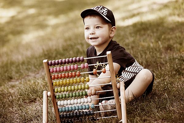 Kinderfoto sitzender Junge mit Cap hinter einem Rechenschieber auf einer Wiese.