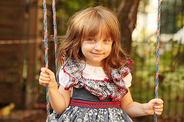 Kinderfoto lächelndes Mädchen in Rüschenkleid auf einer Schaukel.