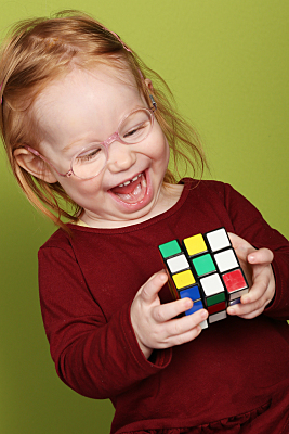 Kinderfoto Portrait lachendes Mädchen mit Brille und rotem Pullover mit einem Bügeleisen in der Hand hinter einem Bügelbrett.