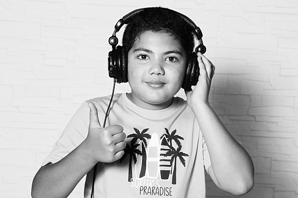 Low Key Kinderfoto Junge mit Kopfhörern auf dem Kopf.