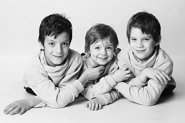 Low Key Kinderfoto von drei, auf dem Bauch liegenden Brüdern, die ihre Hände auf der Schulter des benachbarten Kindes ablegen.