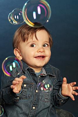 Kinderfoto sitzendes Baby in Jeanshemd, das staunend Seifenblasen anschaut vor dunklem Hintergrund.