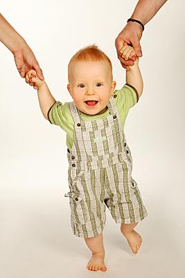 Kinderfoto lächelndes, an den Händen der Eltern gehaltenes Baby.