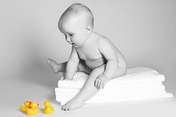 Kinderfoto auf weißen Handtüchern sitzendes, nacktes Baby vor grauem Hintergrund mit gelben Badeenten im Vordergrund.