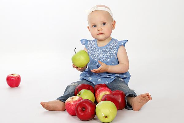 Kinderfoto sitzendes Mädchen mit einem Apfel in der Hand und vielen weiteren Äpfeln vor ihr.