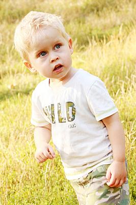Kinderfoto Portrait blonder Junge auf einer Wiese.