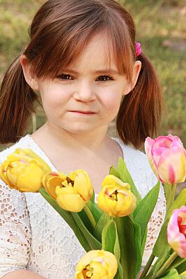 Kinderfoto Portrait Mädchen mit zwei Zöpfen auf einer Wiese.