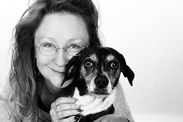 Low Key Tierfoto junge Frau, die ihren kleinen, hellen Hund vor sich hält vor hellem Hintergrund.