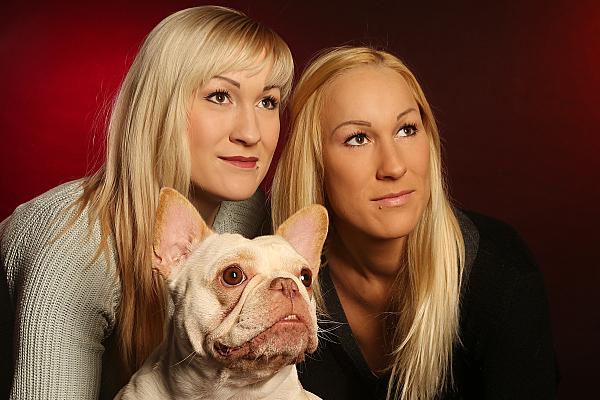 Tierfoto zwei blonde Frauen, die eine Französische Bulldogge zwischen sich haben vor rotem Hintergrund.