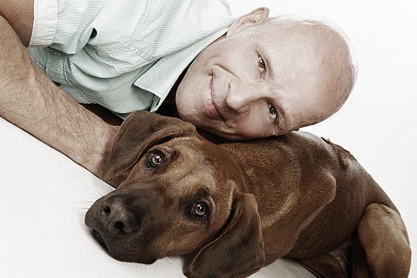 Tierfoto auf dem Bauch liegender Mann, der seinen Kopf auf den neben ihm liegenden Hund ablegt vor hellem Hintergrund.