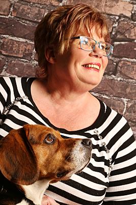 Tierfoto Frau und Hund vor einer Steinwand.