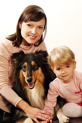 Tierfoto Frau und Kind, die einen Collie zwischen sich umarmen.