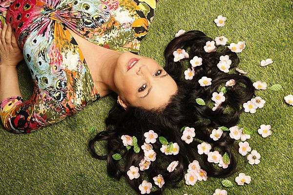 Beautyshooting junge, auf dem Rücken liegende Frau mit dunklen Haaren und rosa Blüten darin.