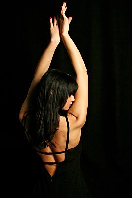 Beautyshooting junge Frau in Rückansicht vor dunklem Hintergrund.