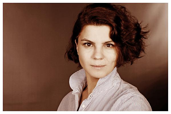 Low Key Bewerbungsfoto Frau mit kurzen, dunklen Haaren vor dunklem Hintergrund,