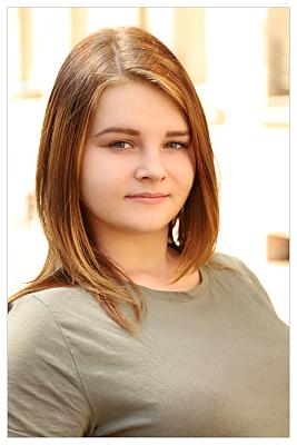 Bewerbungsfoto junge Frau mit offenen Haaren vor Hausfassade.