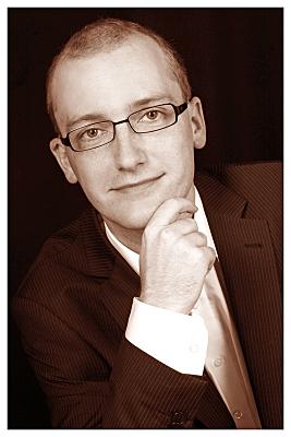 Low Key Bewerbungsfoto Mann mit Brille in weißem Hemd und dunklem Jacket vor dunklem Hintergrund, der eine Hand ans Kinn hält.